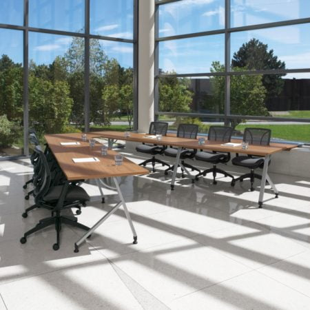 training tables in an open office with large windows and natural light and black chairs