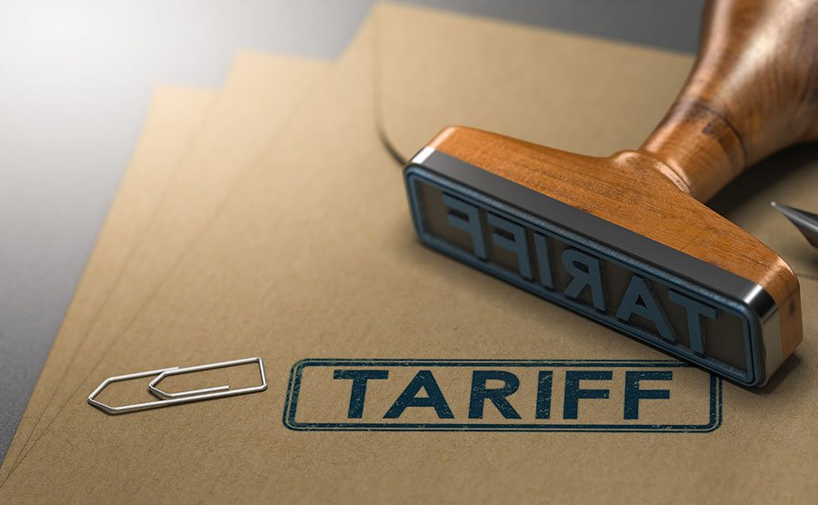stamp with words tariff on it lying on files with a paperclip