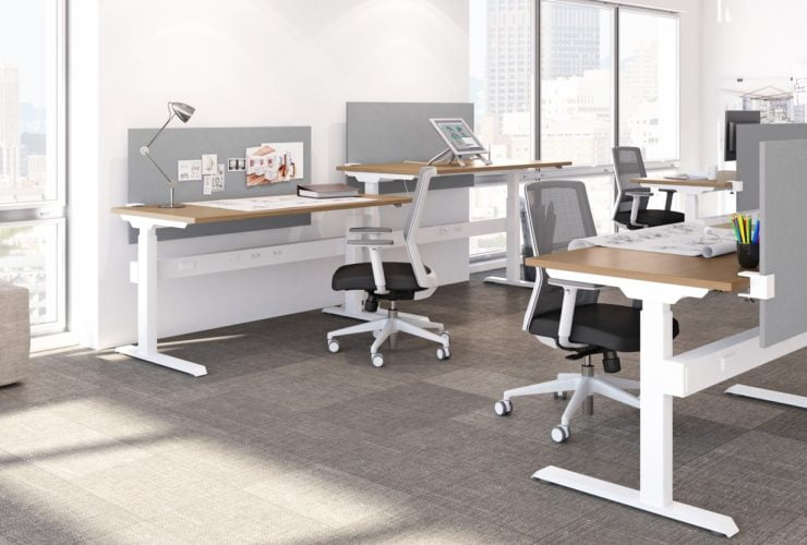 Studio photography of AMQ's KINEX Benching. Two 2-pack single run work spaces facee eachother, each table at a different level. Each one has a walnut colored laminate table top, and grey privacy screens in front of it.