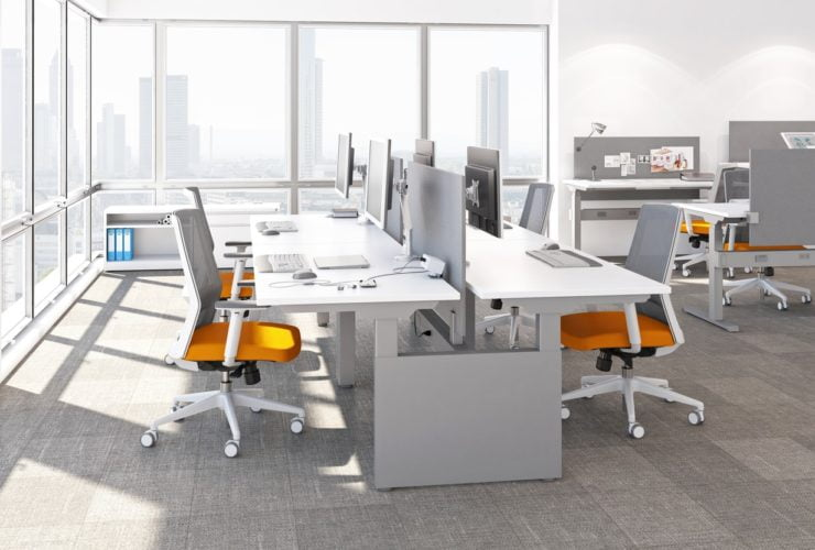 Studio photography of AMQ's KINEX Benching. A 2-Pack double run workspace is at the corner by the window. Another pair of single run is off to the side. Each has a white laminate table top, and adjustable screens.