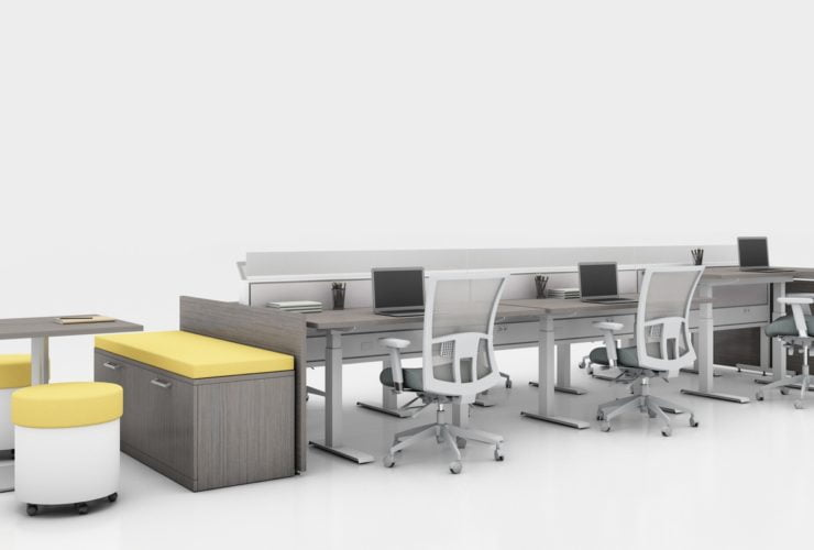 Global's 6-person power beam desks on a white studio set. Each workstation has a laptop open, with glass paneling for privacy. At one end is a cabinet with sunflower yellow cushions, and a square Swap table.