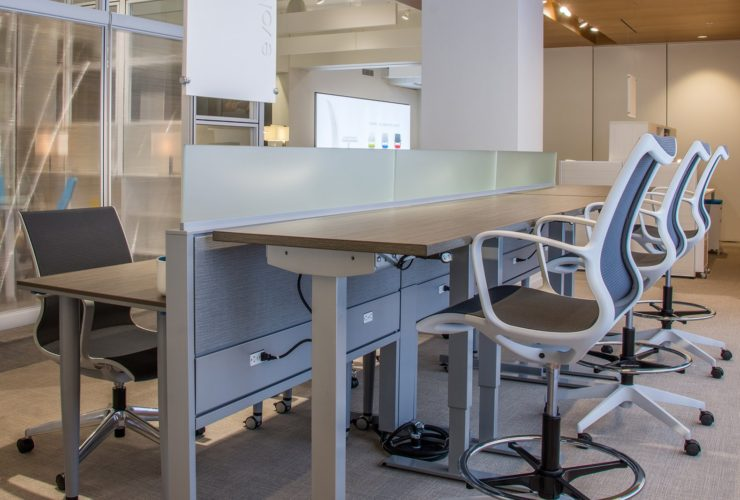Global's 6-person power beam desks in a large office space. Three workstations are set up with the Foil tables adjusted higher than the three workstations facing it.
