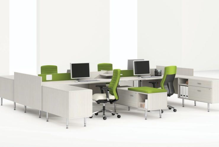 Global's 4-person sidebar benching in a stark white studio set. Each workstation has a flat screen monitor and a green backed rolling chair. The desktop and returns on the side are finished in a white finish.