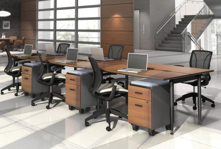 Studio photography of Global's 6-person sidebar benching with a vibrant honey brown finish. Each work station has mobile pedestal drawers and a rolling chair. Beyond, is a flight of stairs and elevator.