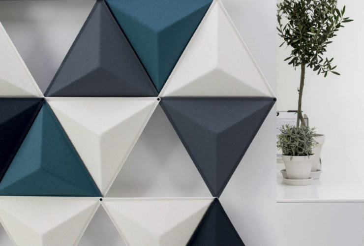 Studio shot of the Aircone acoustic panels in a pale room. This partition uses three different colors of Aircones. The Diagonal sides reveal a white platform with tall potted plants set on top.