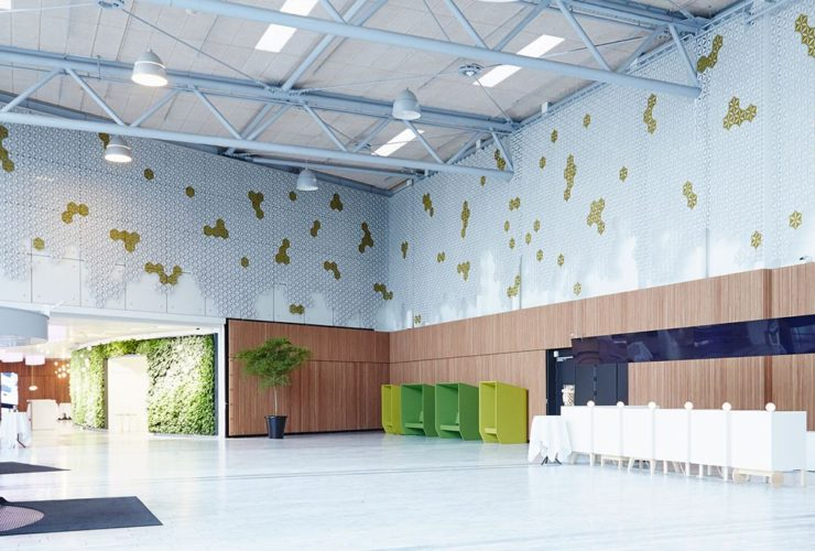 Wide shot inside a large lobby, with Airflake acoustics placed along the upper part of each wall. The studio is hosting other partitions and seating for later display.