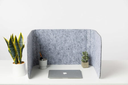 Hide privacy screen, using charcoal colored PET. A laptop is closed, with a few small plants in front of it.