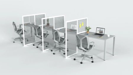 A medium desk set for four office workers. A Hitch partition seperates each station. The work desk nearest to us sports a potted plant. Stick-it notes are place on panel of the first Hitch screen.