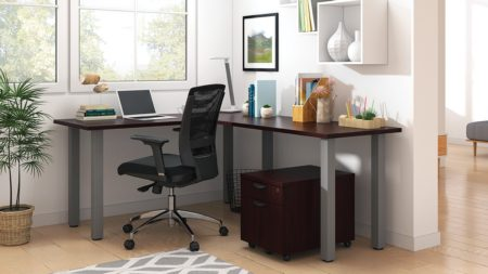 Studio shot of OTG's Home Office, with an L-shaped desk with a tungsten metal frame. The surface is finished in an American Mahogany. A matching set of drawers has been rolled under the desk, at the left of the mesh back chair. To the left of the laptop is a set of books and an OTG LED Desk lamp in the corner.