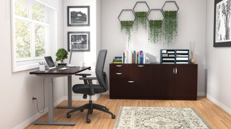 Studio shot of OTG's Home Office Setup, which has a height-adjustable work desk placed at the window. A set of four planters is hung on the wall, above the mixed storage unit. Both surfaces are finished in an American Espresso. A total of four drawers and a double-door cabinet can store different supplies. On top is a set of books, with a giraffe bookend sculpture. A file box to the right holds two columns of slots for important files or as an Inbox.